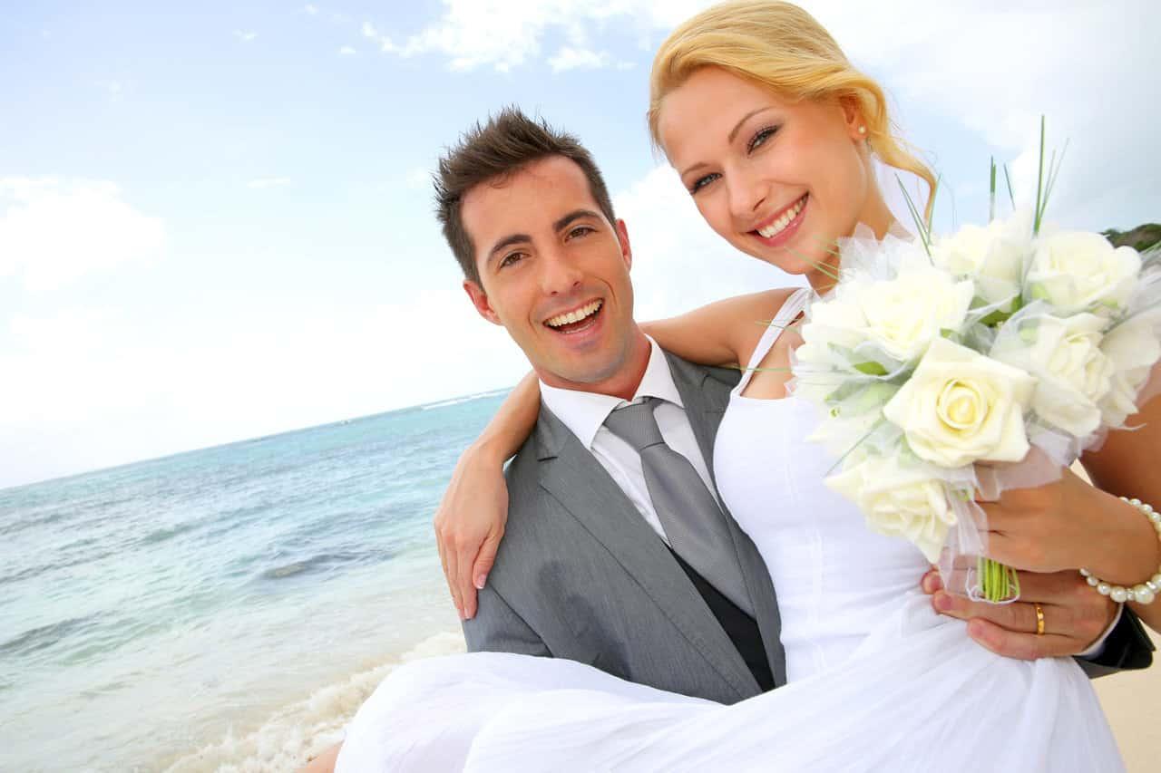 Bräutigam trägt seine Braut auf Händen am Strand